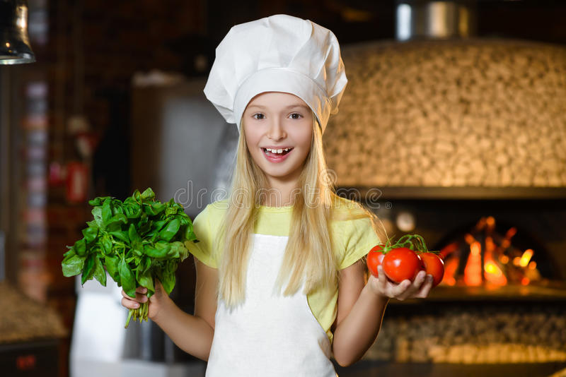 Lustiges lächelndes Chefmädchen, das Tomaten und Basilikum hält lizenzfreies stockfoto