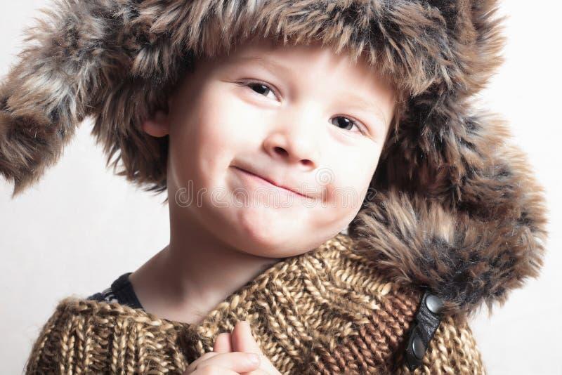 Lustiges lächelndes Kind im Jungen des Pelzes hat.fashion.winter style.little stockfotografie