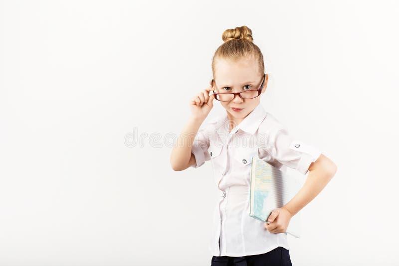 Lustiges lächelndes kleines Mädchen ahmt einen strengen Lehrer gegen Whit nach lizenzfreies stockbild