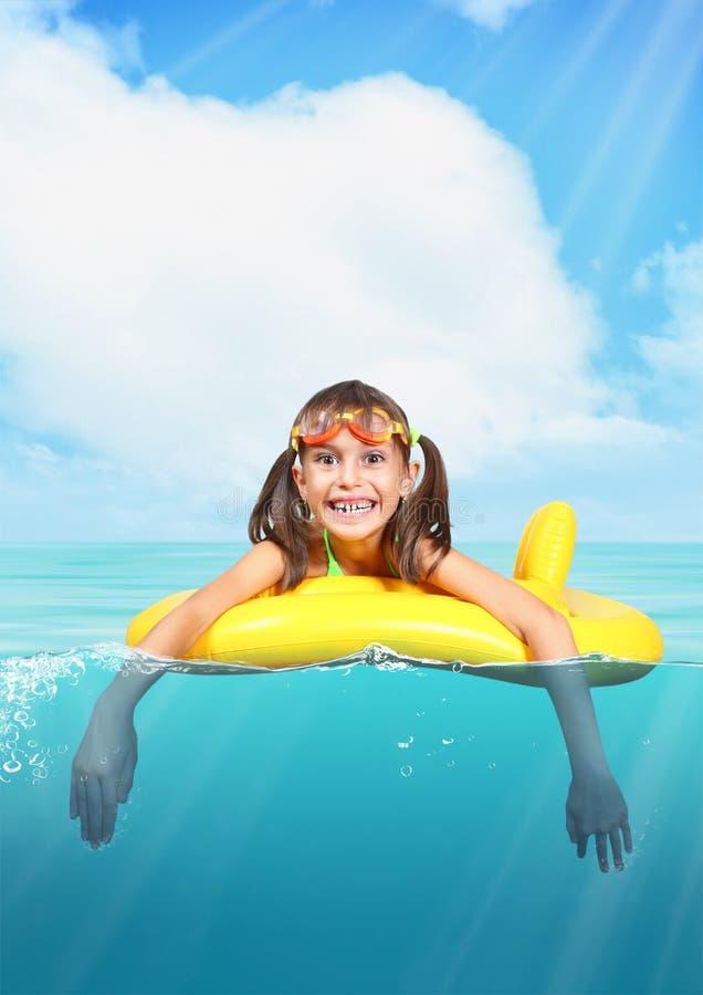Lustiges lächelndes kleines Mädchen mit den tauchenden Gläsern, die inflatabl schwimmen lizenzfreie stockfotografie