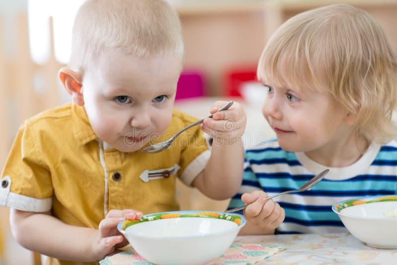 Lustiges lächelndes Kleinkind, das im Kindergarten isst lizenzfreie stockbilder