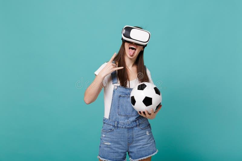 Lustiges Mädchenfußballfan in der Kopfhörergrifffußball-Vertretungszunge, Hörner herauf Geste lokalisiert auf blauem Türkis stockfotos