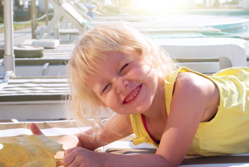 Lustiges Mädchen, das auf Strand ein Sonnenbad nimmt lizenzfreies stockbild