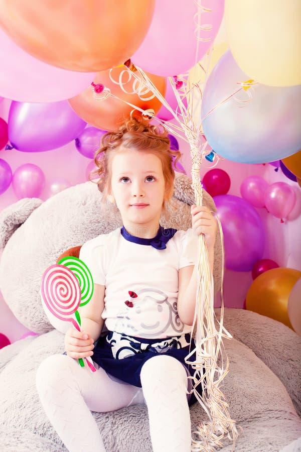 Lustiges Mädchen, das Lutscher und Bündel Ballone hält lizenzfreie stockfotos
