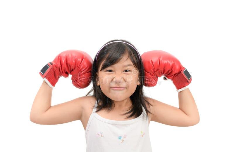Lustiges Mädchen, das mit den roten Boxhandschuhen lokalisiert kämpft stockbild