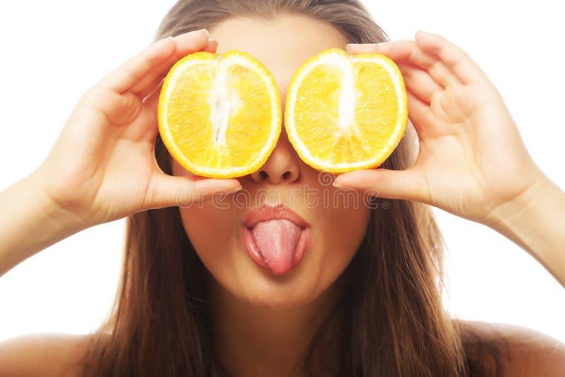 Lustiges Mädchen, das Orangen über Augen hält stockbild