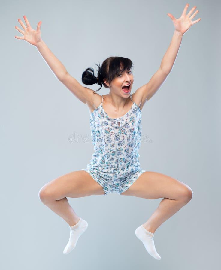 Lustiges Mädchen in den Pyjamas, die für Freude springen stockfoto