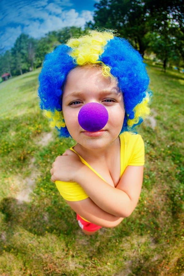 Lustiges Mädchen in der Clownperücke mit blauer Nase stockbilder