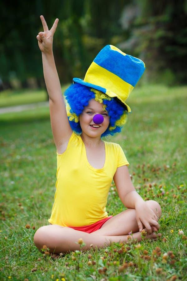 Lustiges Mädchen in der Clownperücke mit blauer Nase lizenzfreie stockfotografie