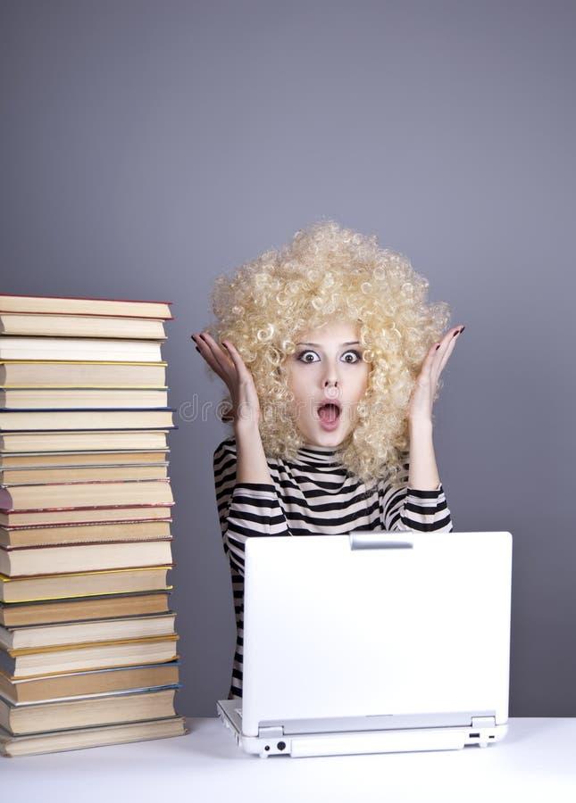 Lustiges Mädchen in der Perücke mit Notizbuch und Büchern. lizenzfreies stockbild