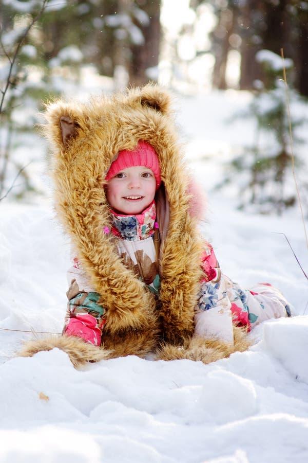 Lustiges Mädchen in einem Pelzhut im Winterwald lizenzfreie stockbilder