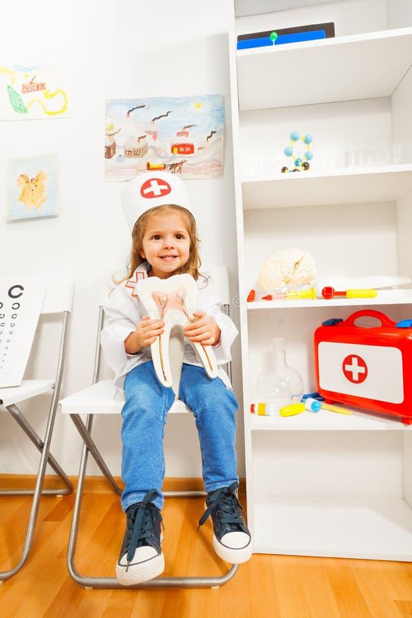 Lustiges Mädchen gekleidet als Zahnarzt am medizinischen Raum lizenzfreies stockfoto