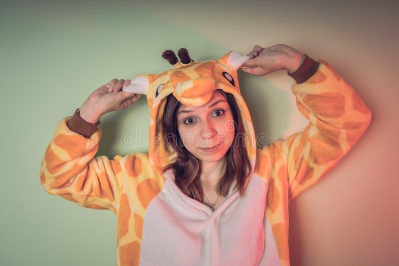 Lustiges Mädchen in kigurumi Pyjamas emotionales Porträt eines Studenten Kostümdarstellung von Kind-` s Trickzeichner Pantoffel i lizenzfreies stockbild