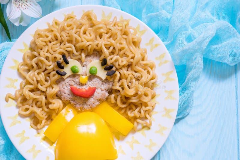 Lustiges Mädchen-Lebensmittel-Gesicht mit Kotelett-, Teigwarennudeln und Gemüse stockfotografie