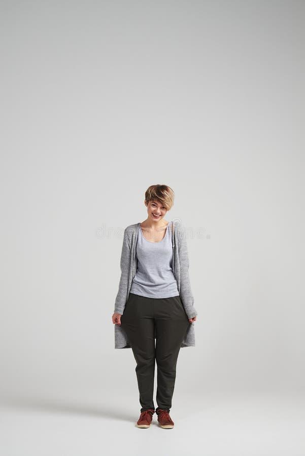 Lustiges Mädchen mit dem kurzen Haarschnitt, der sackartige zufällige Hose trägt stockfotos