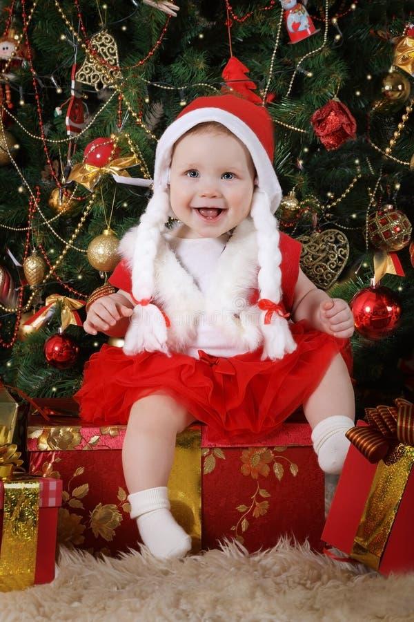 Lustiges Mädchen in Sankt-Kostüm unter dem Weihnachtsbaum lizenzfreies stockfoto