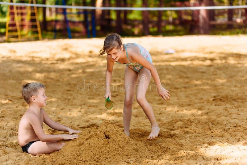 Lustiges Mädchen und Junge begraben ihre Füße im Sand auf dem Strand lizenzfreie stockfotos