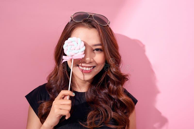Lustiges M?dchen bedecktes Auge mit Lutscher und Lachen ?ber rosa Hintergrund stockfotos