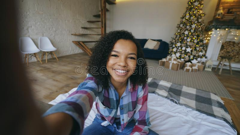 Lustiges Mischrassemädchen, das zu Hause selfie Fotos auf Smartphonekamera nahe Weihnachtsbaum macht lizenzfreies stockbild