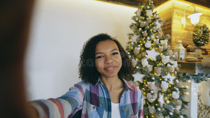 Lustiges Mischrassemädchen, das zu Hause selfie Fotos auf Smartphonekamera nahe Weihnachtsbaum macht stockfotos