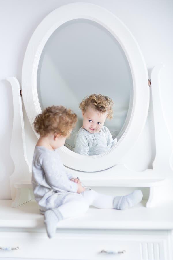 Lustiges nettes Baby, das ihre Reflexion in einem weißen Schlafzimmer aufpasst stockfoto