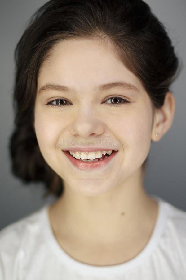 Lustiges nettes lächelndes Blinzeln des jungen Mädchens, die Zunge zeigend, die Kamera über weißem Hintergrund betrachtet stockbild