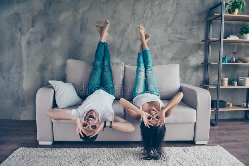 Lustiges Paar mit dem Glasgestikulieren ist das Lügen, das auf umgedreht ist stockbild