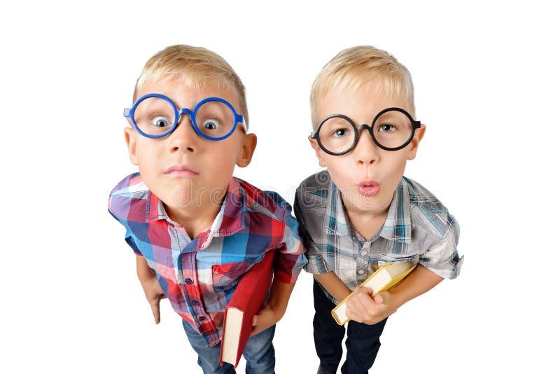Lustiges Porträt der Weitwinkelnahaufnahme des Studenten mit zwei Jungen im Hemd in den Gläsern, die Buch in den Händen, die Kame lizenzfreies stockbild