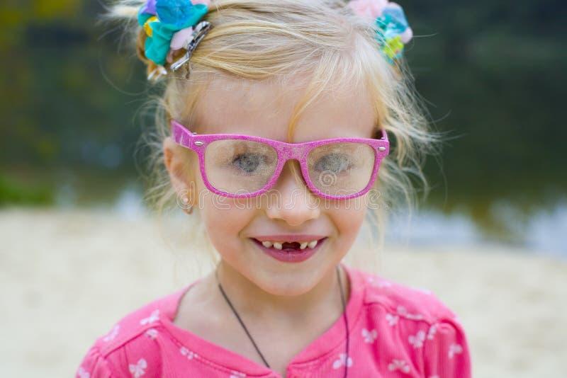 Lustiges Porträt des emotionalen Mädchens in den rosa Gläsern stockbild