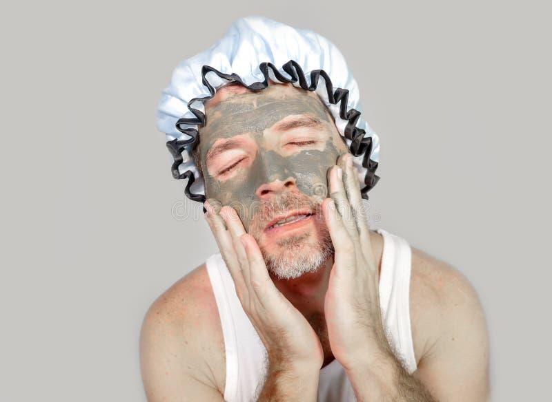 Lustiges Porträt des Lebensstils des glücklichen sonderbaren Mannes auf der Duschkappe, die zu im Badezimmerspiegel mit grüner Cr stockbild