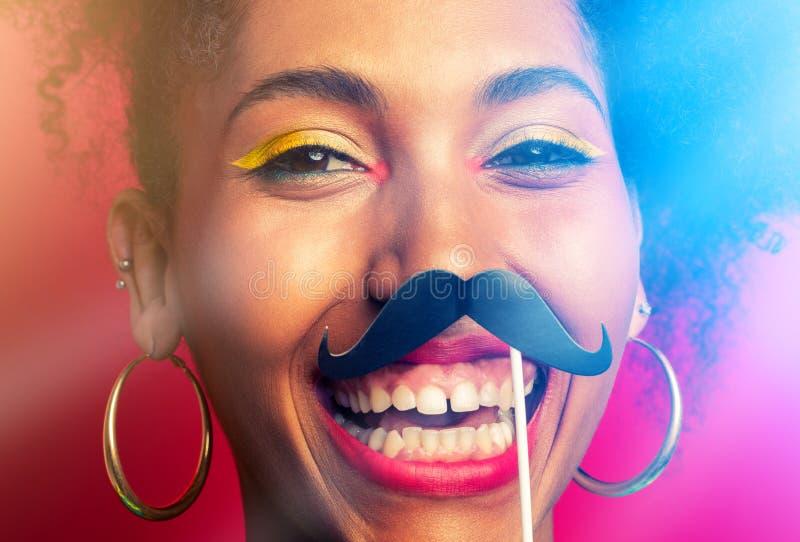 Lustiges Porträt des Mädchens mit dem Pappschnurrbart stockfoto