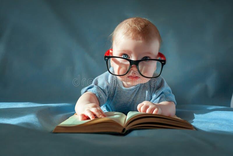 Lustiges Porträt des netten Babys in den Gläsern Das Baby liegt auf seinem Magen und liest ein altes Buch auf einem blauen Hinter lizenzfreie stockfotos