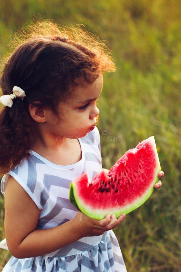 Lustiges Porträt eines unglaublich schönen gelockten kleinen Mädchens, das Wassermelone, gesunden Fruchtsnack, entzückendes Klein lizenzfreies stockbild