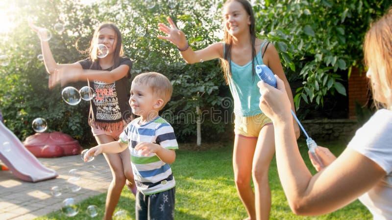 Lustiges Portr?t von gl?cklichen netten jungen Schlagund cathcing Seifenblasen der Familie am Haushinterhofgarten lizenzfreies stockbild