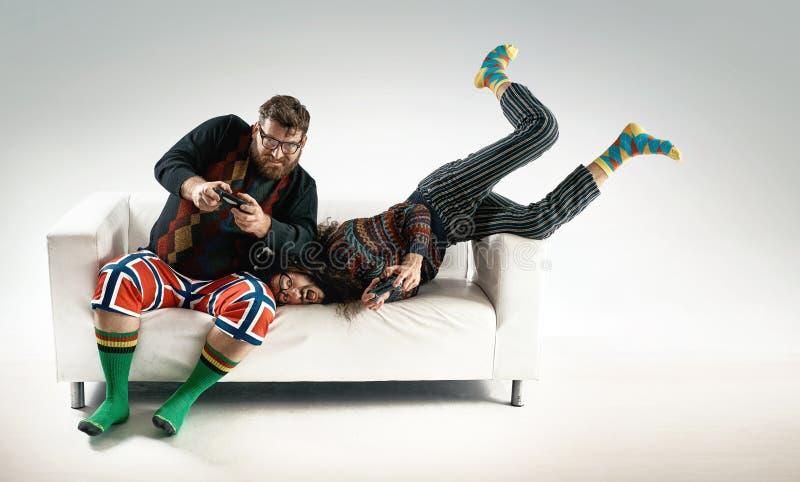 Lustiges Porträt von zwei Freunden, die Konsole spielen stockbilder