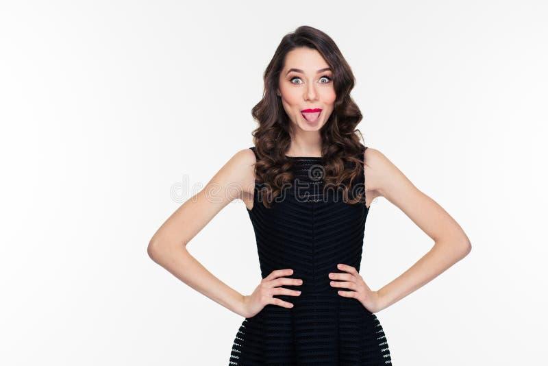 Lustiges reizendes Retro- angeredetes Mädchen im schwarzen Kleid, das Zunge zeigt stockbilder
