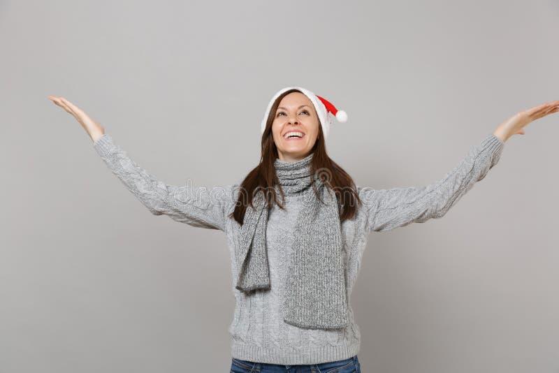 Lustiges Sankt-Mädchen im grauen Strickjackenschal Weihnachtshut, der oben, verbreitend schaut, die Hände zeigend beiseite lokali stockbild