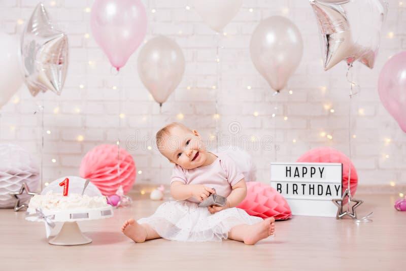 Lustiges schmutziges Mädchen und zertrümmerter Geburtstagskuchen über Backsteinmauer mit Lichtern und Ballonen stockfotografie