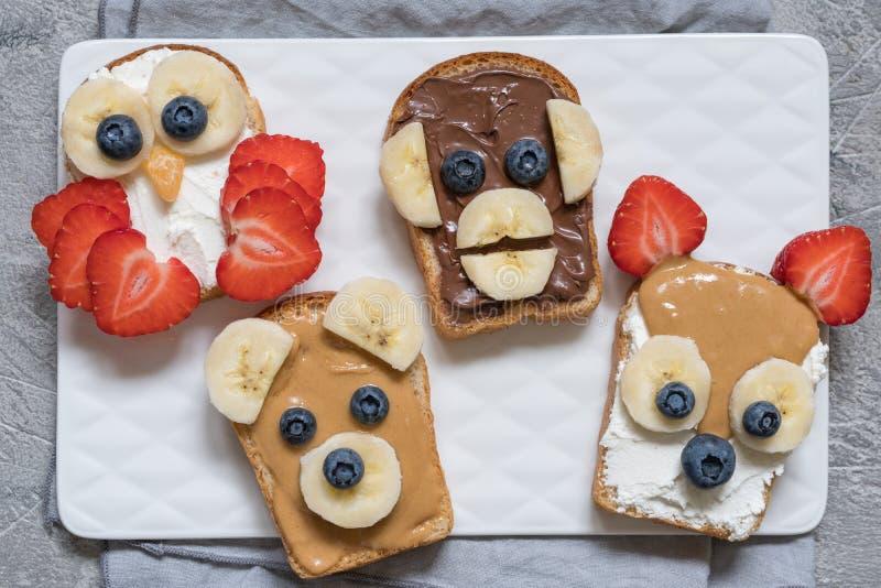 Lustiges Tier stellt Toast mit Banane, Erdbeere und Blaubeere gegenüber stockfoto