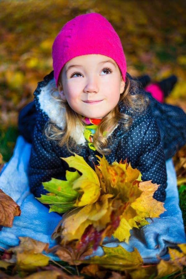 Lustiges träumendes schönes kleines Mädchen, das mit Ahornblättern liegt stockfoto