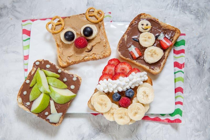 Lustiges Weihnachten stellt Toast mit Banane, Erdbeere und Blaubeere gegenüber stockfoto