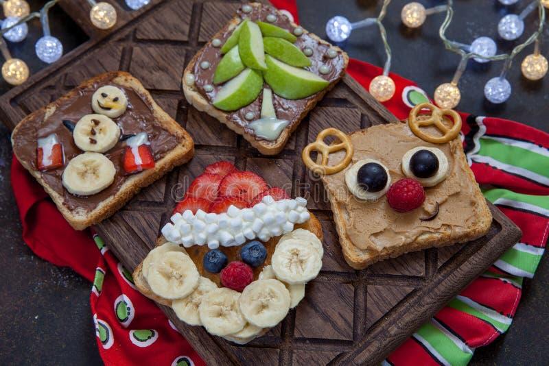 Lustiges Weihnachten stellt Toast mit Banane, Erdbeere und Blaubeere gegenüber lizenzfreie stockbilder
