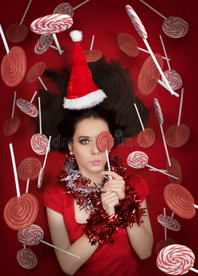 Lustiges Weihnachtsmädchen, das eine Süßigkeit umgeben durch Lutscher hält stockbild