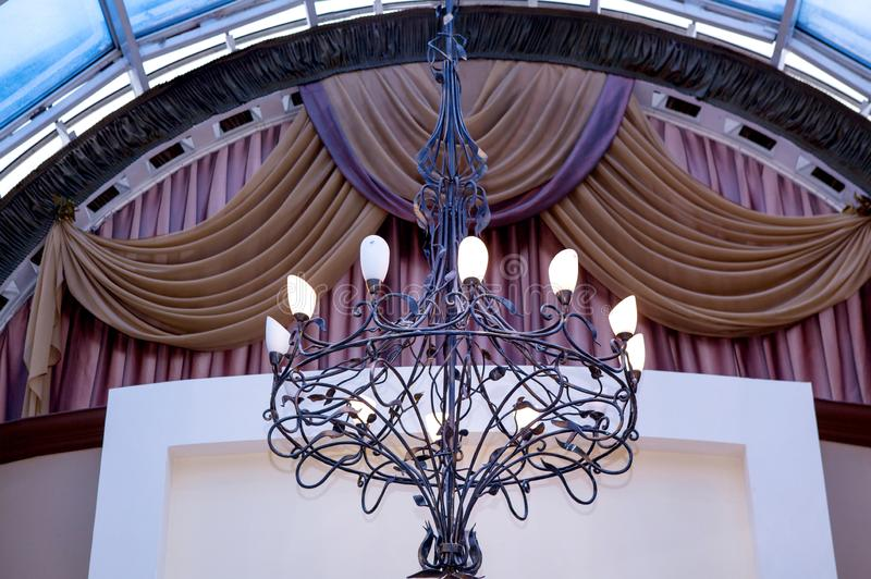 Lustre élégant de fer travaillé sur le plafond contre le contexte des rideaux image stock