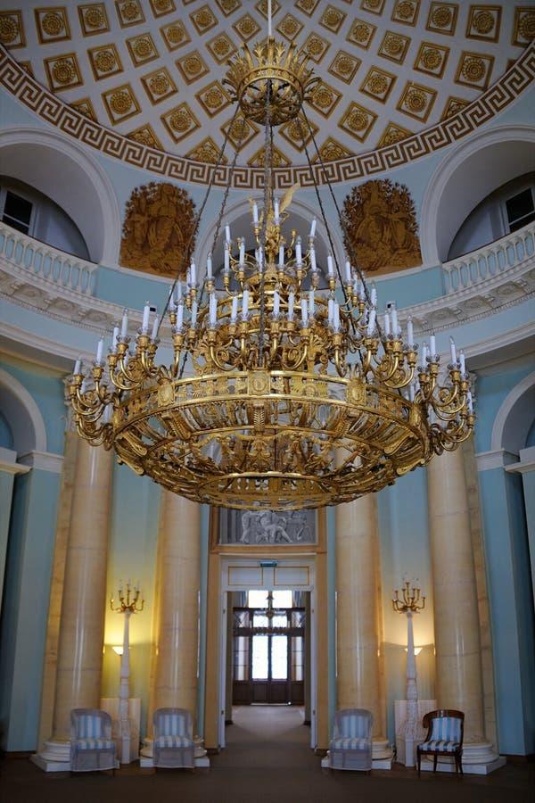 Lustre doré à trois niveaux dans la chambre ovale - le palais grand dedans photographie stock