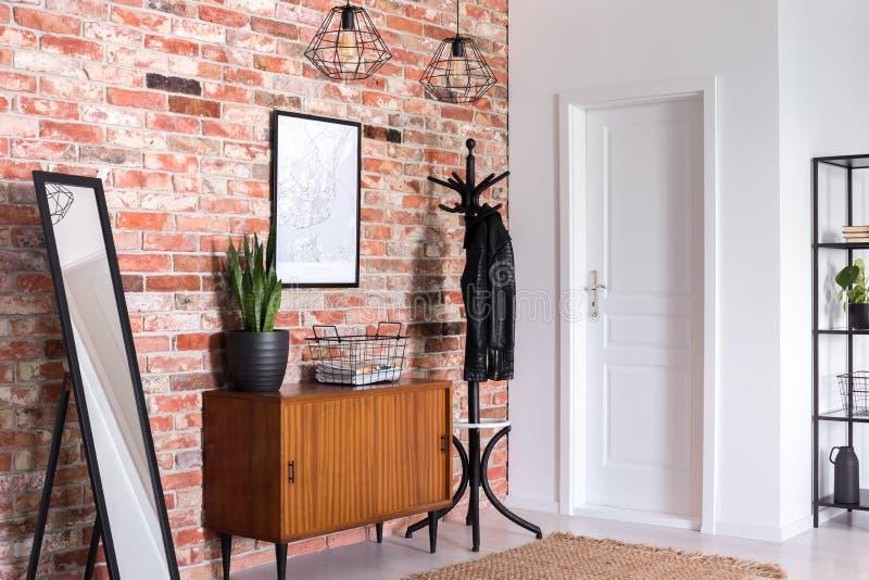 Lustro obok drewnianego gabineta w wejściowej sali wnętrzu z białym drzwi i plakata na czerwonej ścianie z cegieł zdjęcia stock