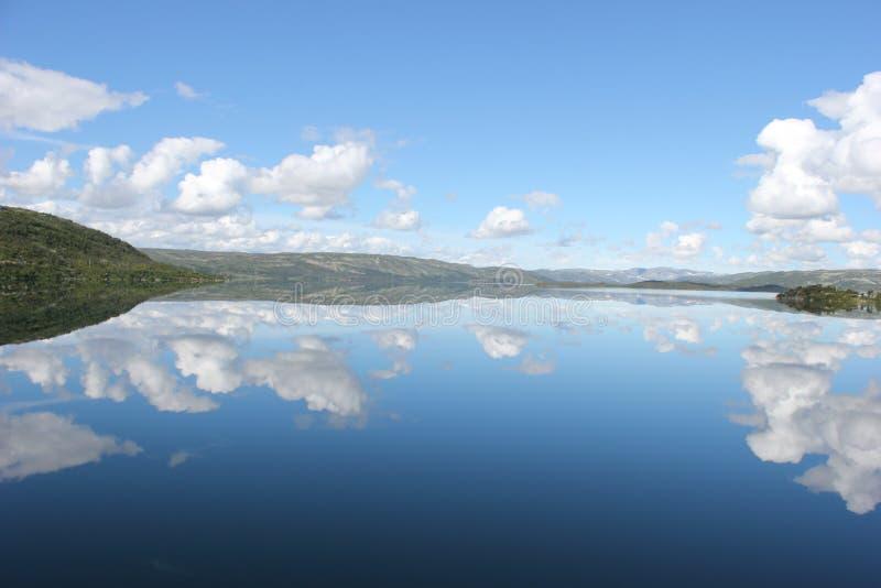 Lustrzany widok niebo, chmury i góra na jezioro wodzie, zdjęcia royalty free