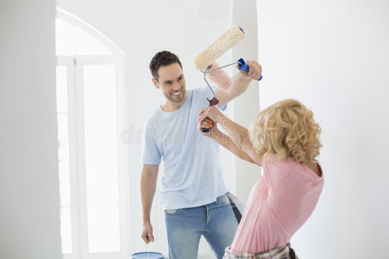 Luta brincalhão dos pares ao pintar a casa nova imagens de stock