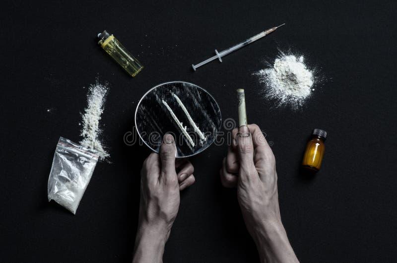 A luta contra drogas e assunto da toxicodependência: as mentiras do viciado da mão em uma tabela escura e em torno dela são droga imagens de stock royalty free