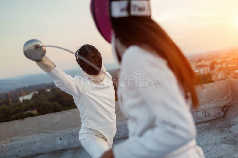 Luta de cerco de dois povos dos atletas no telhado fora imagem de stock royalty free